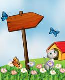 A garden with butterflies and a cat near an arrowboard