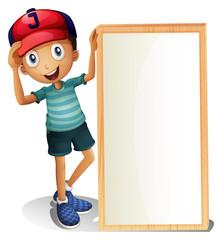 A young boy standing beside an empty signboard