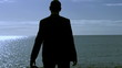 Businessman silhouette standing on a sunny beach in the morning,