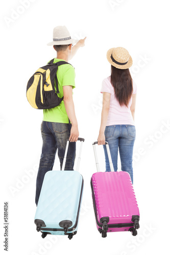 young couple tourist with travel suitcase and pointing something