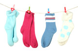 Colorful socks hanging on clothesline, isolated on white