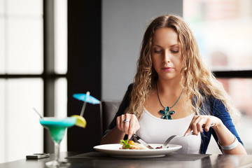 Beautiful young woman dining at a restaurant