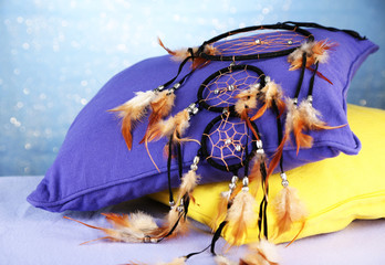 Beautiful dream catcher and pillows on blue background