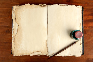 Open old book ink and ink pen on wooden background
