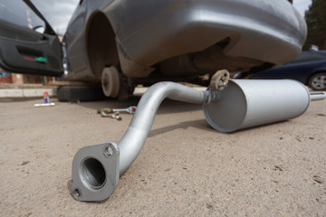 The new muffler against the dirty car