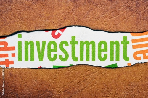 Investment text on torn paper