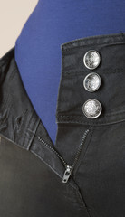 Buttons together with a zip on woman's trousers