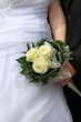 Ślubny bukiet kwiatów, biała suknia, dłonie.