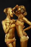 Gilt. Women with Paintbrush. Futuristic Glossy Gold Make-up
