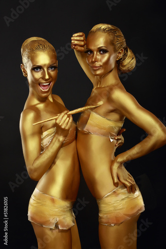 Fancy Dress Party. Women with Golden Metallic Painted Skin