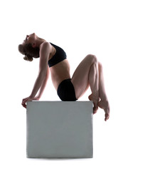 Beautiful woman posing on cube in studio