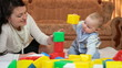 mother playing with her baby boy in bright geometric blocks