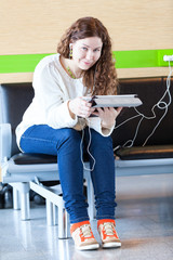 Smiling woman with electronic devices spending time