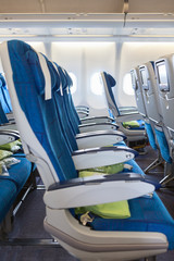 Comfortable seats in aircraft cabin with screens in chairs back