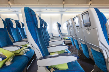 Comfortable seats in cabin of aircraft with screens in chairs