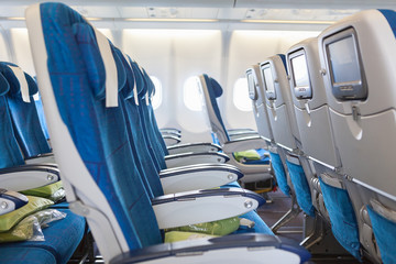 Empty comfortable chairs in cabin of aircraft with screens