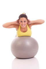young woman exercising on the big gray ball