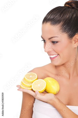 Young woman holding a slice of lemons