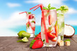 Fresh summer drinks on wooden table with blur sea background