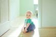Chubby baby boy sitting on wooden floor at home