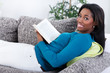 African woman relaxing with a book