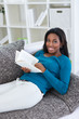Smiling black woman reading book