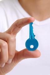 Mano femenina sujetando una llave azul.