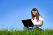 Smiling girl using laptop in nature