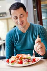 Man eating large portion of salad