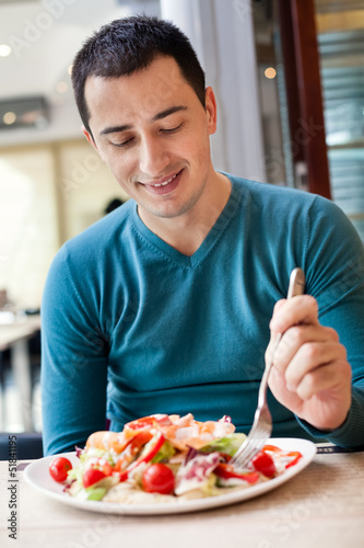 Man eating large portion of salad