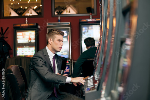 Young man playing the slot machine