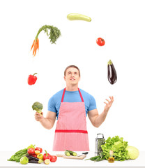 Male with apron juggling with vegetables while preparing food