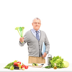 Mature gentleman posing with spoons and a cookbook while prepari