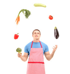 Young handsome male wearing apron and juggling with vegetables