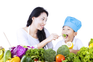 Mother feed young chef