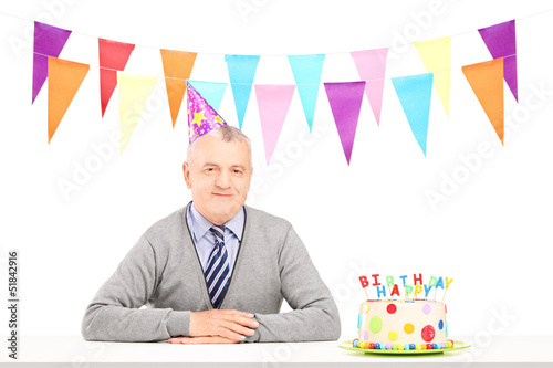 Happy mature gentleman with party hat and a birthday cake