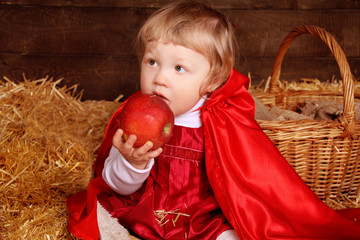 Little girl is sitting on pile of straw eating apple. Little Red
