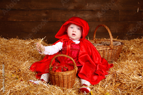 Funny girl is sitting on pile of straw with a basket. Little Red