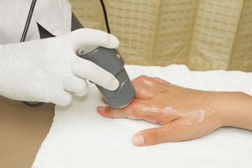 Physiotherapist is applying ultrasound therapy on the hand