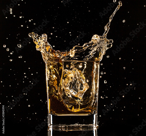 Whiskey splashing out of glass on black background