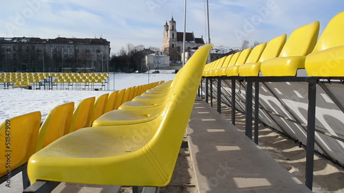 yellow chairs in sunny winter streets and church in the distance