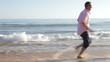 Senior Couple Running Along Beach Holding Hands