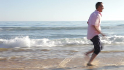 Senior Couple Running Along Beach Holding Hands