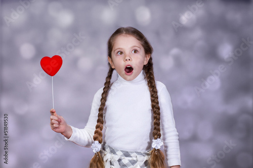 Surprised little girl with heart on a stick