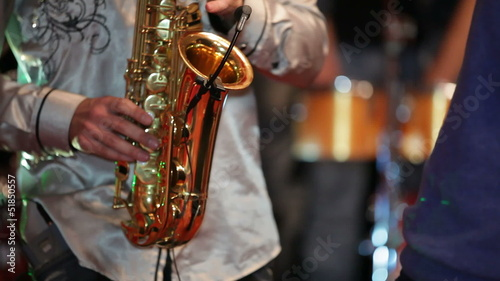 Saxophonist playing at a party while others are dancing