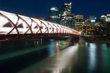 Calgary skyline and pedestrian bridge at night.