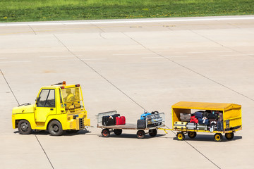 Yellow Freight trolleys with loaded baggage on the runway tarmac