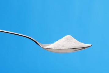 Cucharilla con una porción de azúcar.cuchara de azúcar.