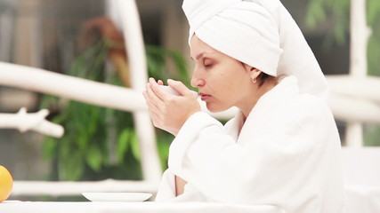Woman drinks morning coffee after shower slowmotion scene