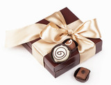 brown box with candies and golden tape on a white background